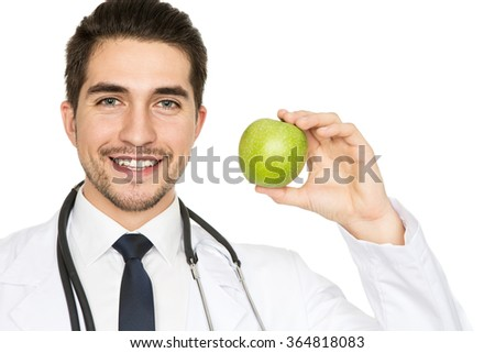 Eat healthy. Closeup portrait of a handsome doctor smiling widely holding an apple  - stock photo