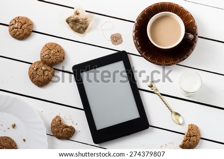Eating and E-Reading. Flourless Walnut Cookies and Black Tea with Milk - stock photo