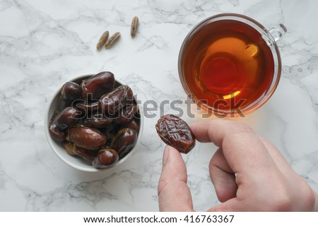 Eating dried dates. Cup of tea on marble table. Traditional arabic food. Top view - stock photo