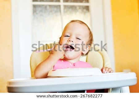eating funny baby girl with  a spoon - stock photo