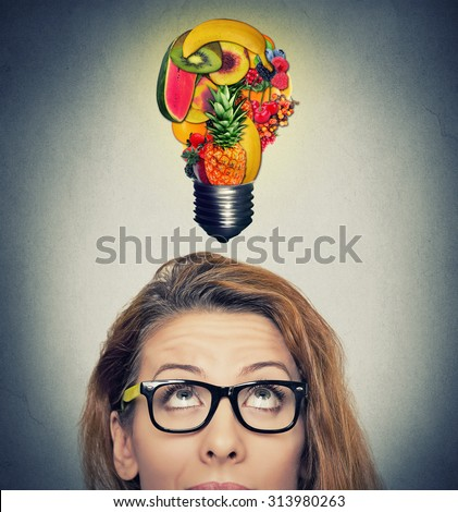 Eating healthy idea and diet tips concept. Closeup portrait headshot woman looking up light bulb made of fruits above head on gray wall background. - stock photo