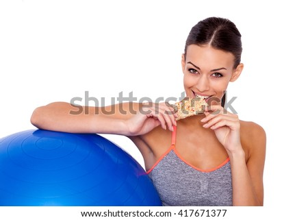 Eating her favorite after-workout snack. Cropped shot of attractive sporty woman sitting next to her fitness ball and eating a protein bar over white isolated background. - stock photo