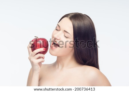 Eating of fascinating red tasty apple gets you feel better all day and gets your beauty attractiveness. Isolated on white background - stock photo