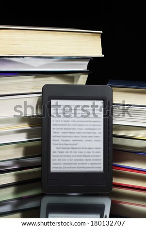 Ebook reader against the background of a stack books - stock photo