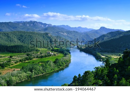 Ebro River passing through Miravet, Spain, with the Serra de Cardo and Els Ports mountain ranges in the background - stock photo
