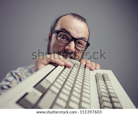 Eccentric angry man bites a keyboard - stock photo