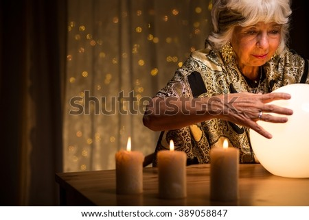 Eccentric old woman looking into crystal ball - stock photo
