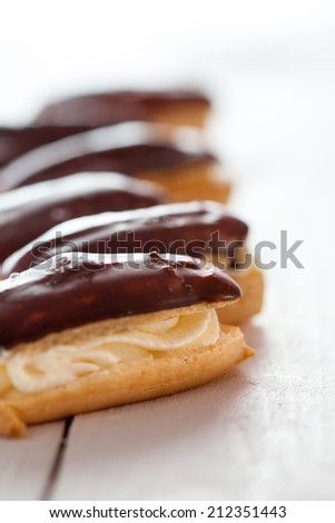 Eclairs filled with whipped cream and topped with icing on a white table - stock photo