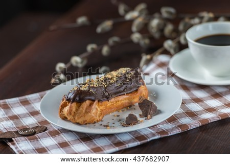 eclairs with chocolate, cream and nuts - stock photo