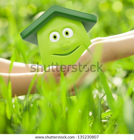 Eco cartoon house in hands against spring green background. Family home concept - stock photo