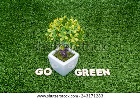Eco concept. Go green words on green grass with small tree - stock photo