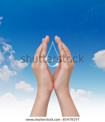 Eco concept : Hand hold water drop with against the blue sky - stock photo