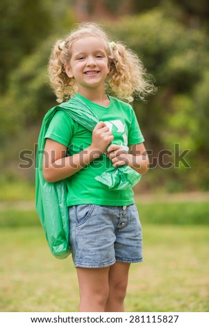 Eco friendly little girl smiling to camera on a sunny day - stock photo