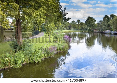 Eco friendly river bank with gentle slope to stimulate growth of wildflowers and swamp vegetation in a recreational park in Soest, Netherlands - stock photo