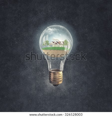 Eco house and energy saving concept in glass light bulb - stock photo