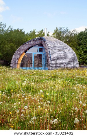eco house made from recycle materials. environmentally friendly home in a field - stock photo