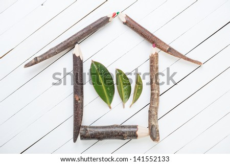 Eco house made up from tree trunk pencils and green leaves - stock photo