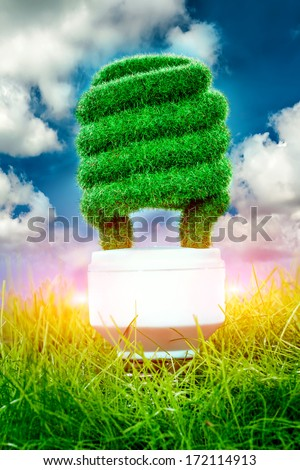 Eco light bulb in green grass on blue sky background - stock photo