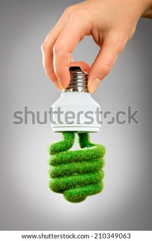 Eco light bulb in hand on gray background - stock photo