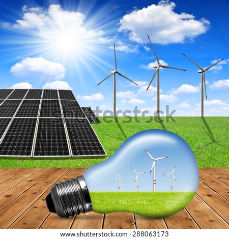 eco light bulb in the background solar panels and wind turbines - Green energy concept - stock photo