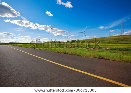 Eco sustainable friendly power generation wind power generator on the prospect of dual carriageway road - stock photo