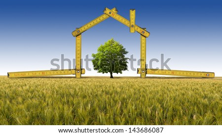 Ecologic House in the Countryside / Wooden yellow meter tool forming a ecologic house in the countryside with tree - stock photo