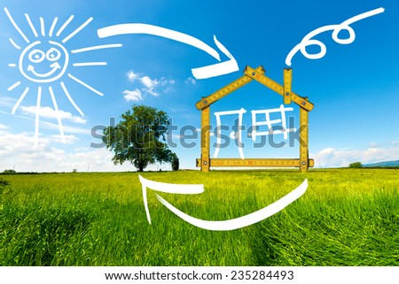 Ecologic House in the Countryside / Wooden yellow meter tool forming a ecologic house in the countryside - stock photo