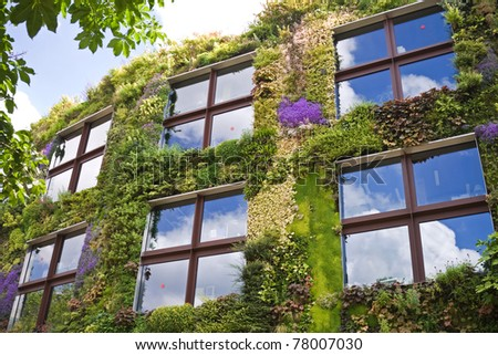 Ecological buildings facade with plans and flower on it - stock photo