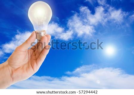 Ecological energy. Hand holds a light bulb against blue sky. - stock photo