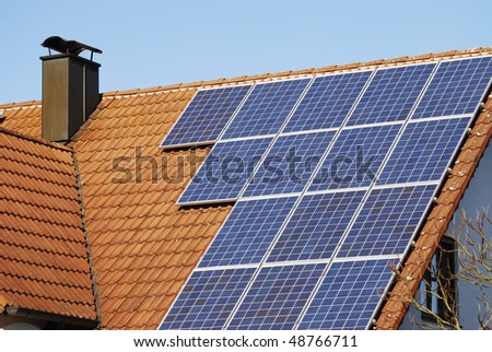 Ecological house roof with solar panels - stock photo