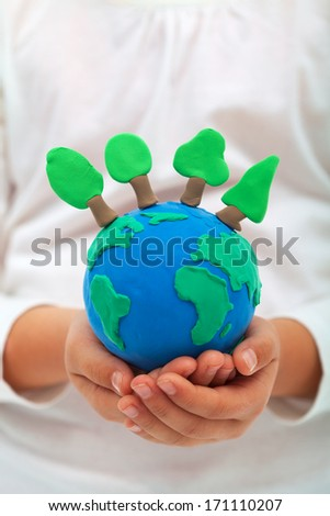 Ecology and environment concept with trees on clay world in child hands - stock photo