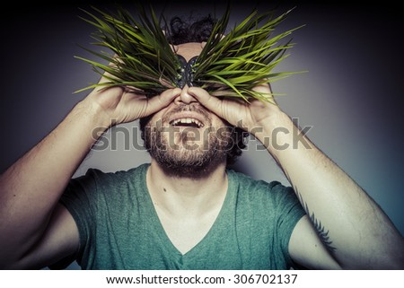 ecology concept, man with green grass in the mouth - stock photo