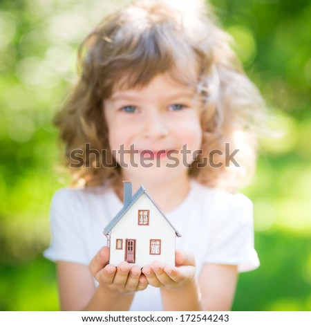 Ecology house in childrens hands against spring green background - stock photo