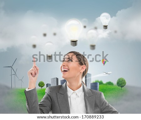 Ecology ideas concept. Businesswoman standing in front of cityscape with lamp overhead - stock photo