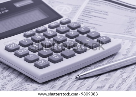 economic newspaper with pen and calculator - stock photo