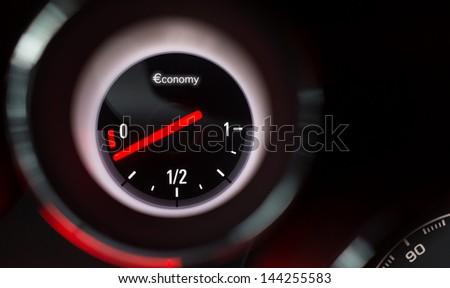 Economy fuel gauge nearing empty. - stock photo