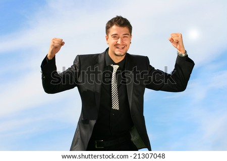 Ecstatic business man has his hands raised. - stock photo
