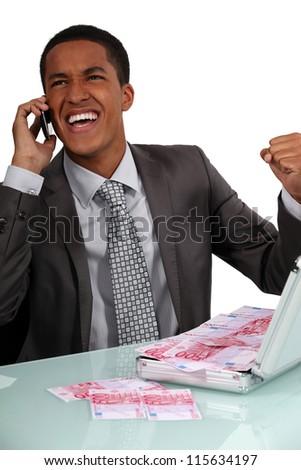 Ecstatic businessman with a briefcase full of money - stock photo