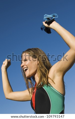 Ecstatic female participant cheering with arms raised against clear sky - stock photo