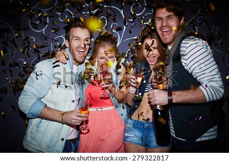 Ecstatic friends with champagne having fun at party - stock photo