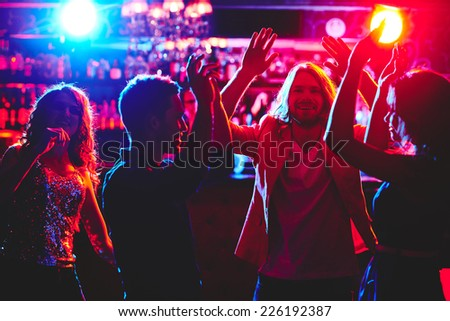 Ecstatic friends with raised arms dancing in nightclub - stock photo