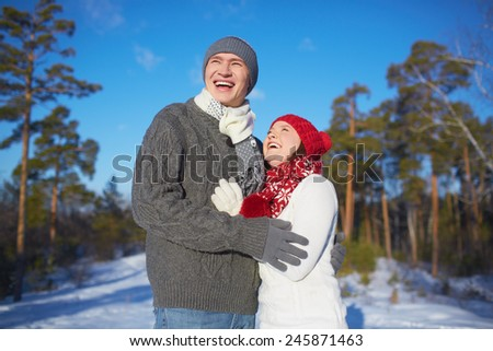 Ecstatic man and woman in knitted winterwear spending leisure in park - stock photo