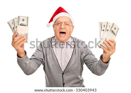 Ecstatic senior gentleman with Santa hat holding few stacks of money and looking at the camera isolated on white background - stock photo