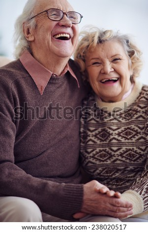 Ecstatic seniors in sweaters laughing - stock photo