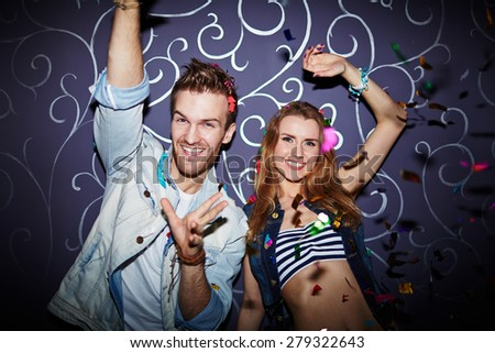 Ecstatic young couple having fun in night club - stock photo