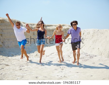 Ecstatic young people holding by hands while running down beach - stock photo