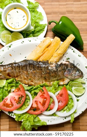 Ecuadorian food series: fried fish on a plate with yucca and salad - stock photo