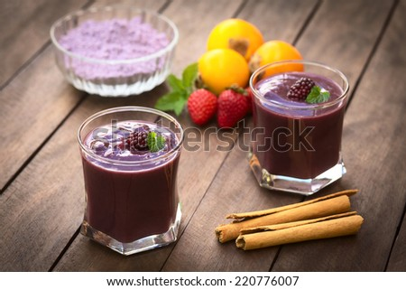 Ecuadorian traditional drink called Colada Morada, prepared by cooking purple corn flour and different fruits, condiments and cane sugar (Selective Focus, Focus on the blackberry on the left drink) - stock photo