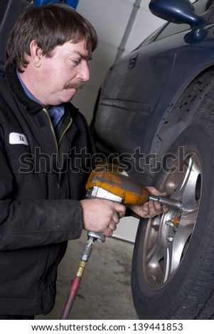Ed takes the lug nuts off aluminum alloy wheel for a routine brake check - stock photo