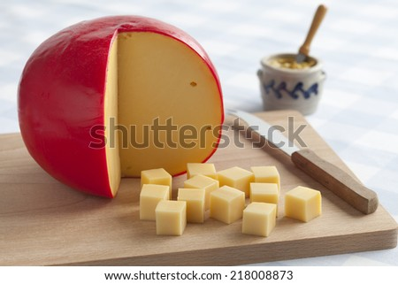 Edam cheese and cubes on a cutting board - stock photo